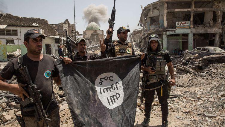 A Mossoul, en Irak, des soldats américains et irakiens arborent un drapeau pris à l'Etat islamistes après des combats, le 2 juillet 2017. (LAURENCE GEAI / SIPA)