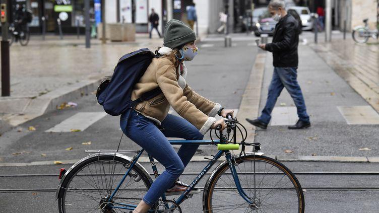 Une femme circulant à vélo dans le centre-ville de Saint-Etienne (Loire), le 22 octobre 2020. (PHILIPPE DESMAZES / AFP)