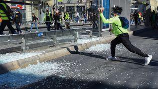 """Un manifestant brise la vitre d'un arrêt de tramway lors de la manifestation des """"gilets jaunes"""" à Montpellier le 23 mars 2019. (SYLVAIN THOMAS / AFP)"""