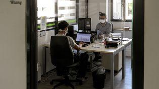 Deux salariés, avec masques et séparés par du plexiglas, dans une entreprise deVenissieux, près de Lyon, en aout 2020. (MAXIME JEGAT / MAXPPP)