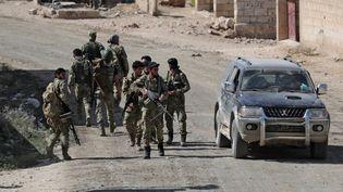 Des combattants syriens participant à l'offensive de la Turquie près de la ville frontalière de Tal Abyad (Syrie), le 12 octobre 2019. (KHALIL ASHAWI / REUTERS)