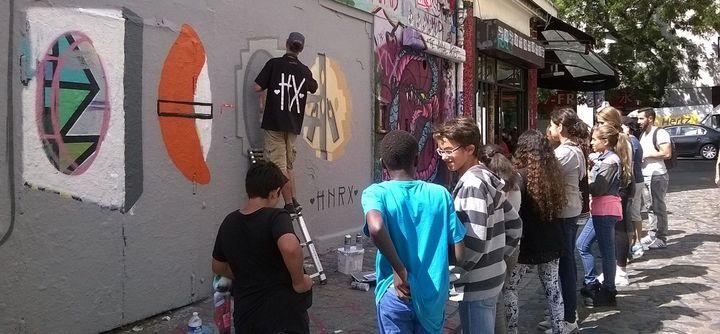 Le street artiste HNRX en plein travail dans la rue Dénoyez, à Paris.  (Claire Digiacomi / Culturebox)