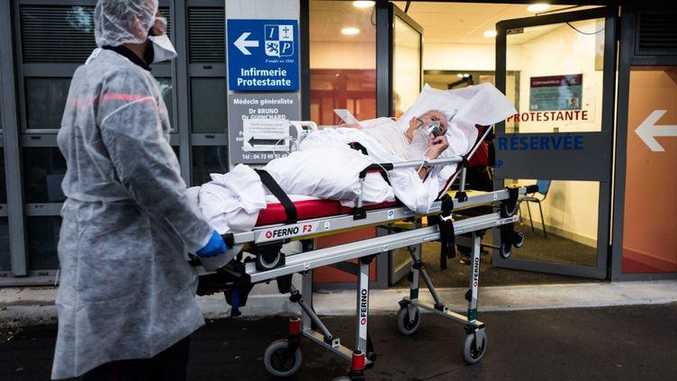 Le personnel soignant en train de transférer un patient atteint du Covid-19 au secteur de réanimation à l'infirmerie protestante de Lyon, le 18 avril 2020. (NICOLA VIGILANTI / HANS LUCAS / AFP)