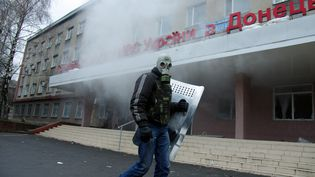 Un militant pro-russe participe à la prise d'un bâtiment officiel à Horlivka, dans l'est de l'Ukraine, le 14 avril 2014. (ALEXEY KRAVTSOV / AFP)
