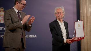 Peter Handke applaudi par le président serbe Aleksandar Vucic lors de la cérémonie de remise del'une des plus grandes décorations de la Serbie, le 9 mai 2021 (OLIVER BUNIC / AFP)