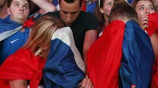 """Des supporters de l'équipe de France à la """"fan zone"""" de Paris, après la défaite des Bleus face au Portugal, dimanche 10 juillet 2016. (BENOIT TESSIER / REUTERS)"""