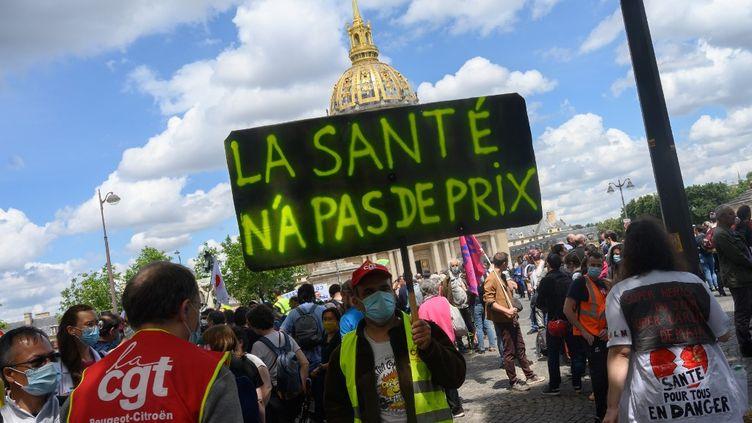 """Un manifestant portant un masque brandit une pancarte """"La santé n'a pas de prix"""" lors d'un rassemblement du personnel soignant le 16 juin 2020. (ESTELLE RUIZ / HANS LUCAS)"""