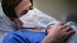 Un père tient son enfant dans ses bras à la maternité, le 17 novembre 2020 àl'hôpital des Diaconesses, à Paris. (MARTIN BUREAU / AFP)