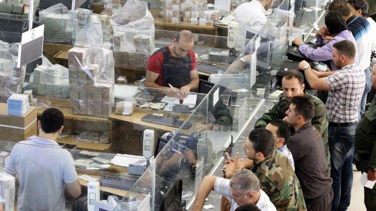 Des Syriens attendent à la banque le versement de leurs salaires après l'injection, le 30 juin 2015, de nouveaux billets de 1000 livres par la Banque centrale de Syrie. (AFP PHOTO/ Louaï Beshara)