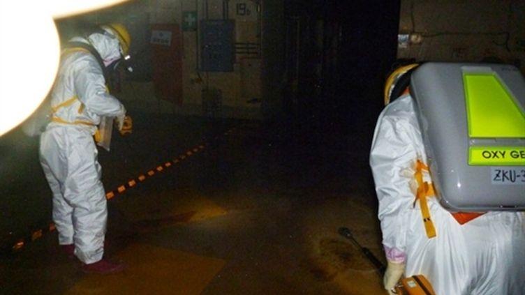 Des employés pénètrent dans l'enceinte du réacteur n°2 de la centrale de Fukushima, le 18 mai 2011. (AFP - Tepco)