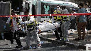 Des secouristes israéliens transportent un corps sur une civière le 13 octobre 2015 à Jérusalem-Est, après une attaque contre un bus. (THOMAS COEX / AFP)