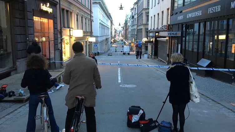 Deux cyclistes se tiennent devant une rue barrée, dans le centre-ville deStockholm (Suède), le 7 avril 2017. (REUTERS)