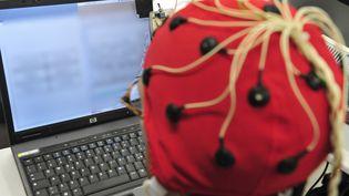 Des électrodes sont posées sur le crâne d'un individu pour capter des signaux de son cerveau. (GIUSEPPE CACACE / AFP)