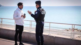 Un policier non masqué contrôle un passant, le 18 mars 2020 à Nice (Alpes-Maritimes). (ARIE BOTBOL / HANS LUCAS / AFP)