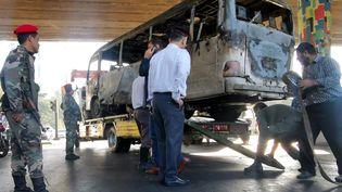 Le bus carbonisé après une attaque matinale contre un bus de l'armée ciblé par des engins explosifs, à Damas (Syrie), le 20 octobre 2021 (AFP)
