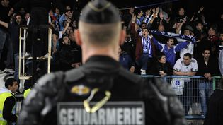 Un gendarme mobile fait face aux supporters auxerrois qui protestent contre la direction du club, le 20 mai 2012, au stade de l'Abbé-Deschamps, à Auxerre. (JEFF PACHOUD / AFP)