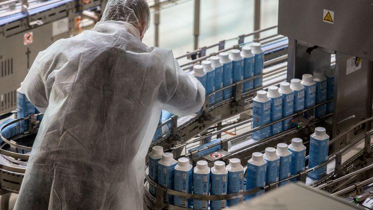 Un employé travaille sur la chaîne de production de l'usine de la société Eau Neuve (O9) produisant des briques d'eau minérale, le 7 juin 2021 à Merens-les-Vals (Ariège). (FRED SCHEIBER / AFP)