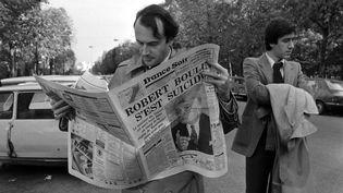 """Un homme lit le journal """"France Soir"""", à Paris, le 30 octobre 1979, jour de l'annonce de la mort de Robert Boulin. (GEORGES BENDRIHEM / AFP)"""