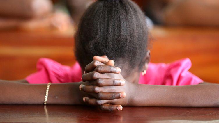 Une jeune togolaise se recueille lors de la messe dominicale dans une église de Lomé, le 16 juillet 2017. (PASCAL DELOCHE)