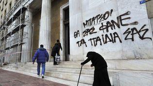 Des messages de protestation contre les mesures d'austérité sur la façade de la Banque de Grèce à Athènes, le 14 février 2012. (LOUISA GOULIAMAKI / AFP)