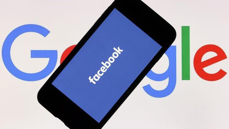 Photo d'illustrationd'un écran de téléphone portable affichant le logo de Facebook devant un écran d'ordinateur affichant l'icône Google à Ankara, en Turquie, le 21 décembre 2020. (HALIL SAGIRKAYA / ANADOLU AGENCY / AFP)