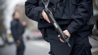 Un policier de la Brigade de recherche et d'interventiontient une arme de service, le 8 janvier 2015, à Montrouge (Hauts-de-Seine), après le meurtre d'une policière municipale. (NICOLAS MESSYASZ/SIPA)
