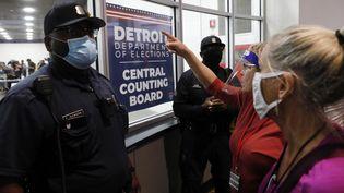 Des policiers font face à des supporters de Donald Trump rassemblés devant une salle de dépouillement des bulletins de vote de l'élection présidentielle, à Détroit (Michigan), le 4 novembre 2020. (JEFF KOWALSKY / AFP)