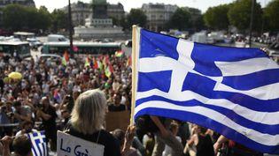 Une manifestante brandit le drapeau de la Grècelors d'une manifestation de soutien au peuple grec, jeudi 2 juillet 2015, place de la Bastille à Paris. (LOIC VENANCE / AFP)
