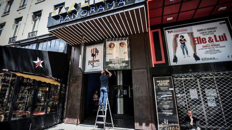 Un employé du cinéma Max Linder prépare les affiches avant la réouverture du cinéma le 22 juin. (STEPHANE DE SAKUTIN / AFP)