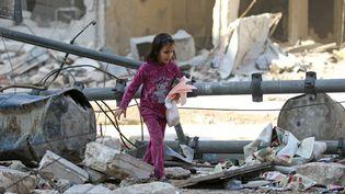 Une fillette dans les décombres dans un quartier d'Alep (Syrie) tenu par les rebelles, le 17 novembre 2016. (d'ABDALRHMAN ISMAIL / REUTERS)