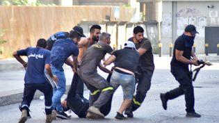 Des hommes emportent le corps d'un de leurs camarades après l'échange de coups de feu qui ont eu lieu à Tayouné, dans la banlieue sud de Beyrouth (Liban), lors d'une manifestation organisée par les mouvements chiites Hezbollah et Amal, le 14 octobre 2021. (- / AFP)