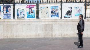 Un homme se tient devant les affiches des élections municipales organisées le 15 mars, le 16 avril 2020, à Marseille. (FABIEN DUPOUX/ SIPA)