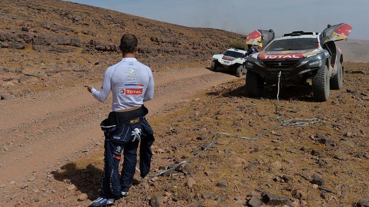Sébastien Loeb attend de l'aide pour remorquer la Peugeot 2008 DKR lors de la 1ère étape du rallye du Maroc