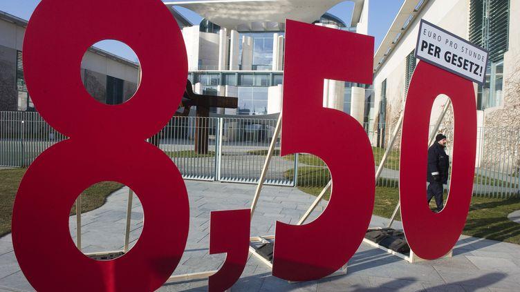 Un panneau réclamant 8,50 euros de l'heure de salaire minimum, devant la Chancellerie, à Berlin (Allemagne), le23 février 2011. (JOHN MACDOUGALL / AFP)