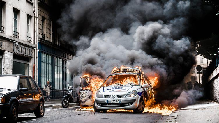 Une voiture de police incendiée par des manifestants, le 18 mai 2016 à Paris. (SIMON GUILLEMIN / HANS LUCAS / AFP)