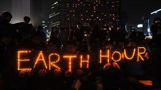 """Des étudiants sud-coréens participent à la manifestation """"Earth Hour"""", samedi 23 mars à Séoul. (KIM JAE-HWAN / AFP)"""