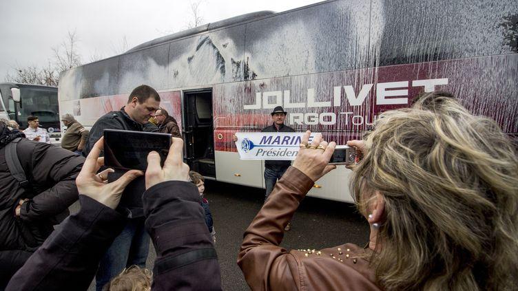 Des militants du Front national photographient un bus dégradé par des opposants à la tenue d'un meeting de Marine Le Pen à Nantes, le 26 février 2017. (MARTIN BERTRAND / AFP)