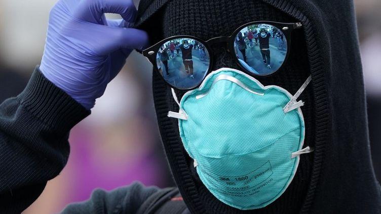 Un manifestant masquédéfile à New York (Etats-Unis), le 1er juin 2020, pour réclamer après la mort de George Floyd à la suite de son arrestation à Minneapolis. (TIMOTHY A. CLARY / AFP)