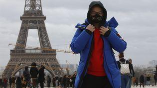 Un homme devant la Tour Eiffel à Paris, le 29 février 2020. (MEHDI TAAMALLAH / NURPHOTO / AFP)