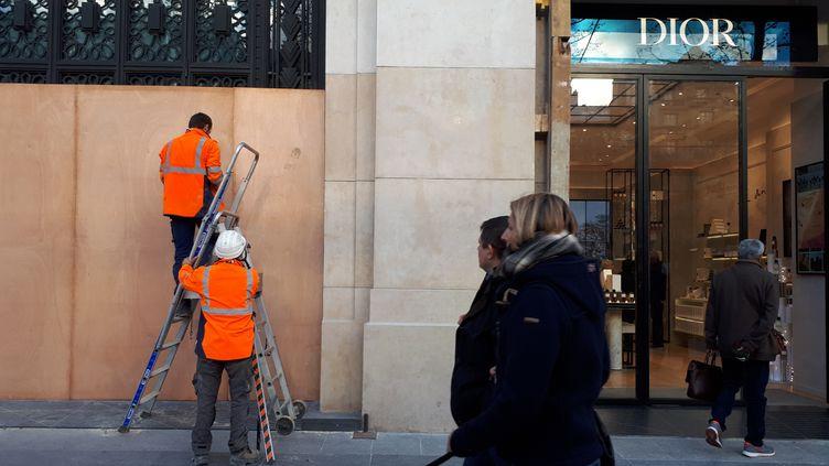 """Des commerçants des Champs-Élysées, à Paris,installent des protections en bois à la veille de la mobilisation des """"gilets jaunes"""" du 1er décembre 2018. (BENJAMIN ILLY / FRANCE-INFO)"""