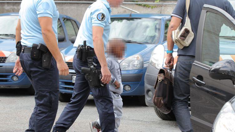 Le petit Rifki est accompagné par des gendarmes en gare de Libourne (Gironde), le 16 août 2015,après avoir été enlevé pendant plus de 25 heures par un ravisseur. (MAXPPP)