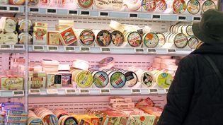 Une cliente devant le rayon camemberts d'un supermarché à Caen (Calvados), le 20 mars 2012. (CHARLY TRIBALLEAU / AFP)