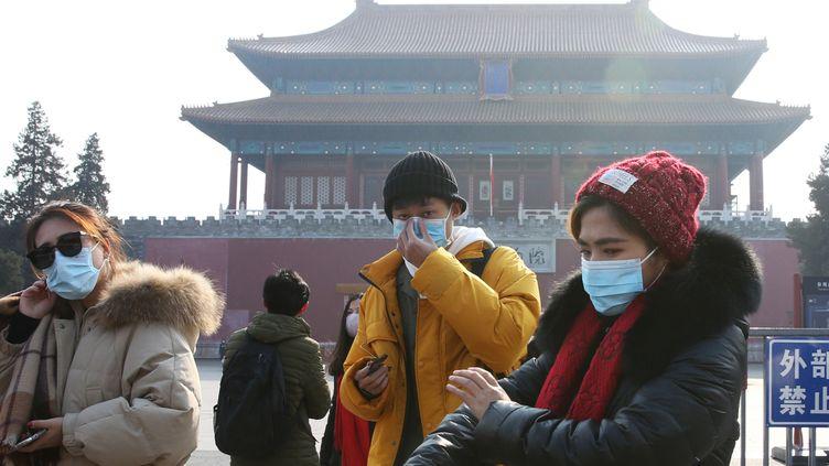 Des personnes avec des masques le 25 janvier 2020, devant la Cité interdite, à Pékin (Chine), fermée pour éviter la propagation du coronavirus. (KOKI KATAOKA / YOMIURI / AFP)