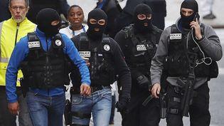 Des policiers cagoulés marchent dans une rue de Saint-Denis, le mercredi 18 novembre 2015. (PETER DEJONG / AP / SIPA)