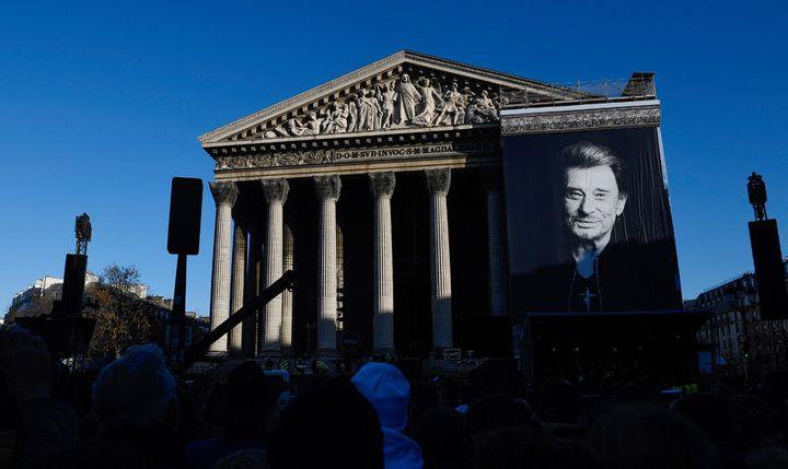 De nombreux fans attendent à l'église de la Madeleine où un portrait géant de la star est affiché (9 décembre 2017)  (Éric Feferberg / AFP)