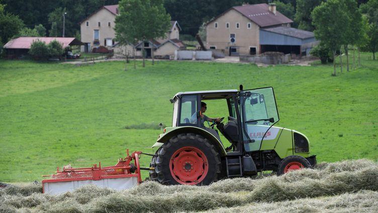 Un tracteur devant une ferme dans le Val d'Amour (Jura). Photo d'exposition. (JEAN PIERRE AMET / MAXPPP)
