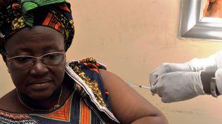 Une femme se fait vacciner contre le virus Ebola, à Conakry (Guinée), lors de tests cliniques, le 10 mars 2015. (CELLOU BINANI / AFP)