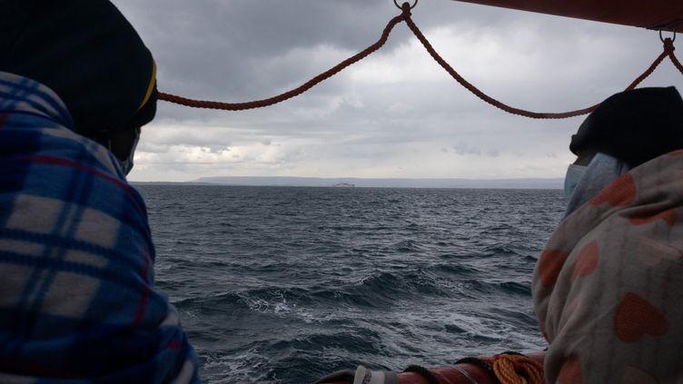 Deux migrants regardent la mer sur le bateau Ocean Viking, affreté par l ONG SOS Mediterranee, le 23 mars 2021 (JEREMIE LUSSEAU / HANS LUCAS / AFP)