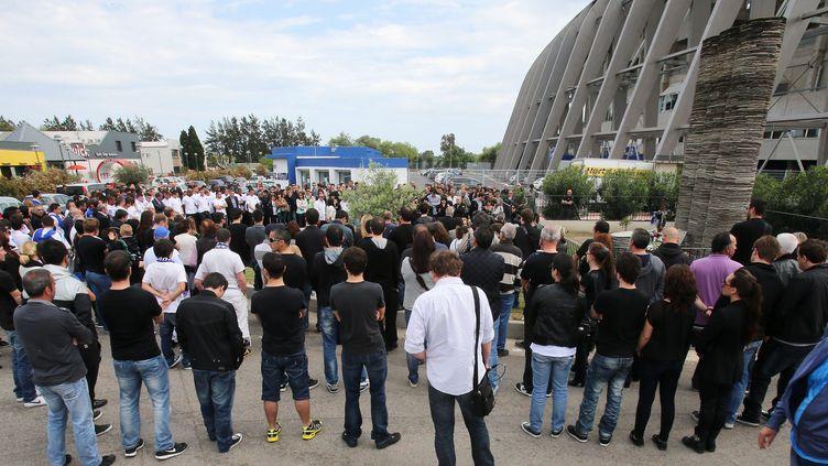 Des personnes se recueillent devant la stèle en mémoire aux victimes mortes dans l'effondrement de la tribune nord du stade Armand-Cesari de Furiani (Haute-Corse), vingt et un ans après le drame, le 5 mai 2013. (MAXPPP)