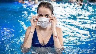 Une jeune femme porte un masque dans la piscine d'un centre thermal, à Cabourg (Calvados), le 27 juin 2020. (LAURE BOYER / HANS LUCAS)